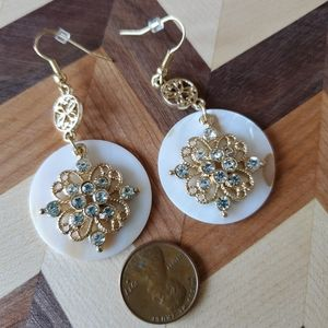 Gold tone dangle with shell in back.